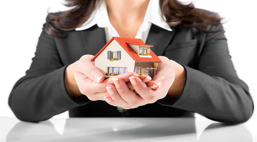 woman holding small house in hands
