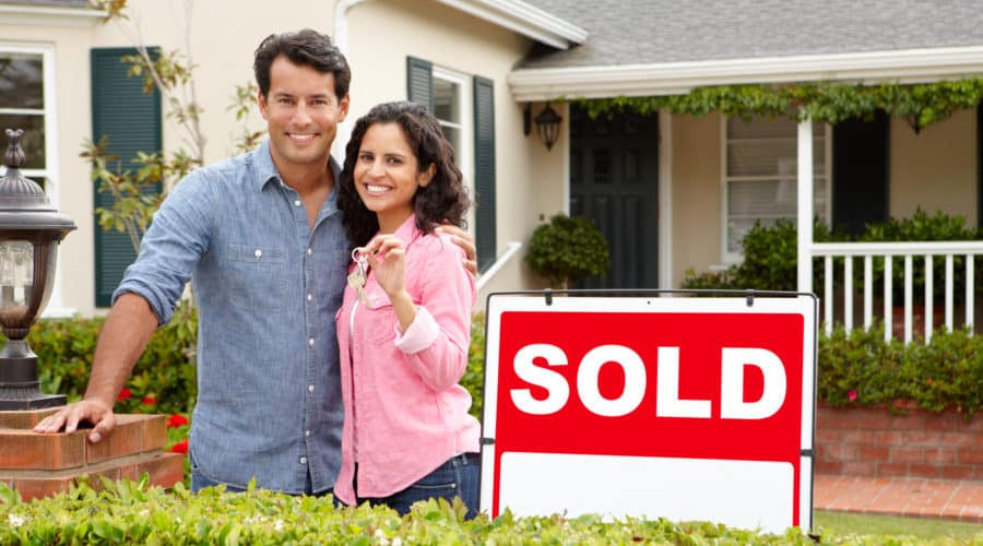 couple in front of home sold sign